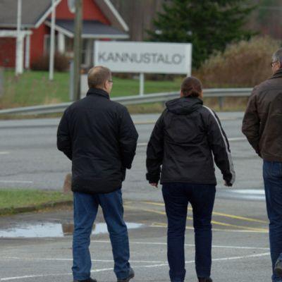 Kolme miestä kävelee poispäin, taustallla Kannustalon kyltti