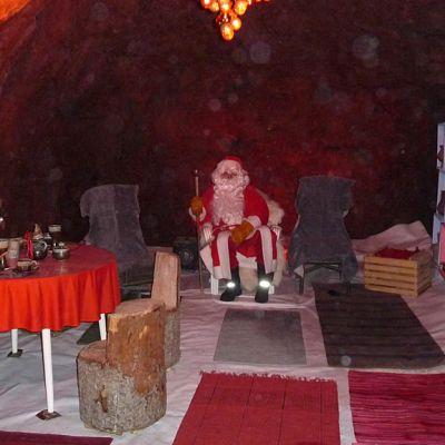 joulupukki istuu joulupukin tuvassa kotkan kallioluolassa