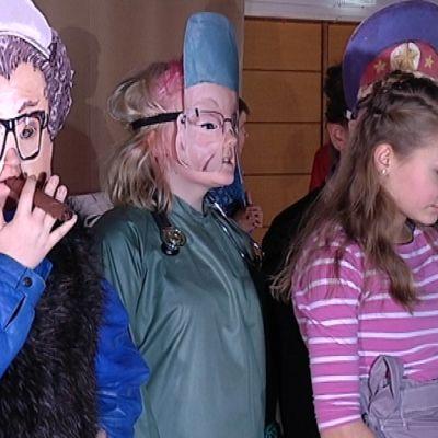 Nuoret seisovat naamait päässä näytelmässä
