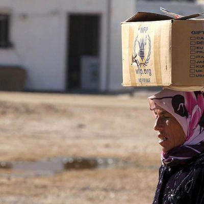 Nainen kantaa avustusjärjestön pakettia päällään.