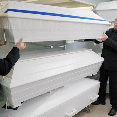 Miehet nostavat arkkua hautaustoimistossa.