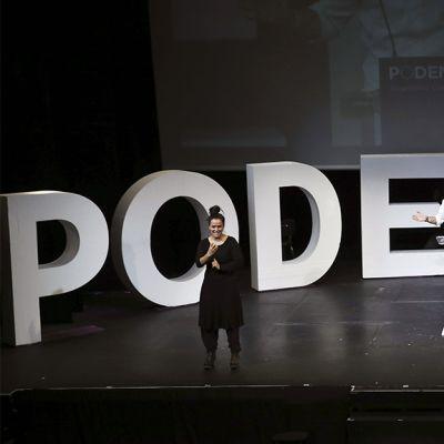 Kaksi henkilöä lavalla suuren Podemos-kirjainten edessä.