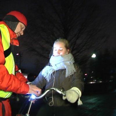 Markku Eilola-Jokivirta kiinnittää valaisinta polkupyörään.