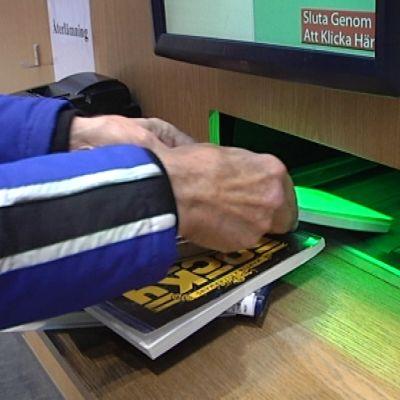 Henkilö palauttaa kirjoja palautusautomaatin kautta.