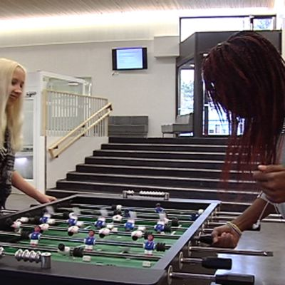 Nuoret pelaavat pöytäjalkapalloa kuolun aulassa.