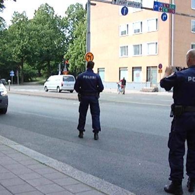 Poliisi valvoo liikennettä ja toinen ottaa valokuvaa