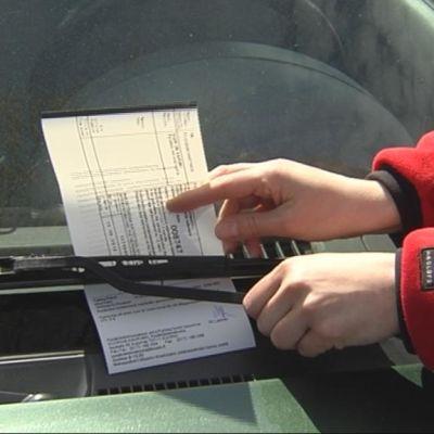 Pysäköinninvalvoja asettaa sakkolapun auton tuulilasiin.
