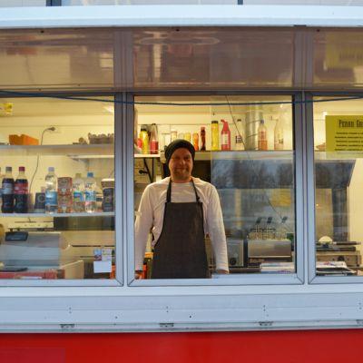 Suomussalmelainen Janne Autere seisoo lähiruokagrillissään ja kurkistaa myyntiluukusta.