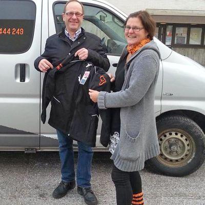 LC Kajaanin sihteeri Raimo Tikkanen lahjoitti erityisnuorisotyöntekijä Tarja Vehkaojalle Saapas-takit vapaaehtoisten käyttöön.