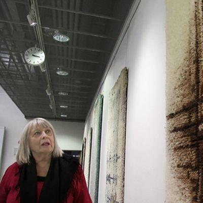 Kuva tulkki kertooo ryijystä taidenäyttelyssä
