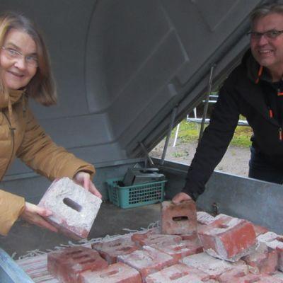 Raila Vainonen ja Rauno Pousi esittelevät Summan tehtaan entisen piipun tiiliä. Satakunta tiiltä on tarkoitus jakaa sukulaisten kesken