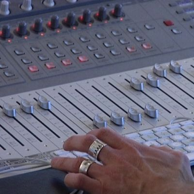 Käsi äänipöydän päällä