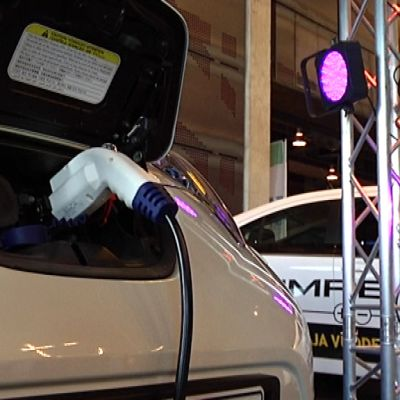 Sähköauto kiinnitettynä latauspistokkeeseen.
