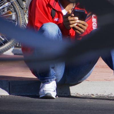 Mies istuu kivetyksellä ja selaa kännykkää.
