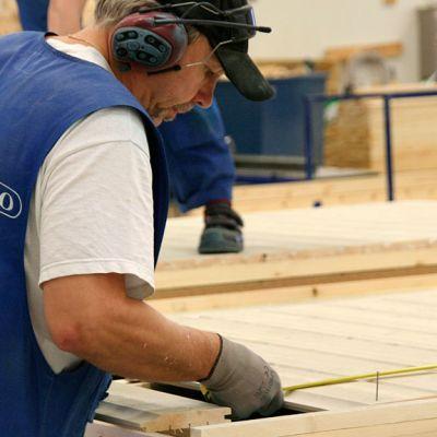Kuvassa talopaketin tekoa kannustalon tehtaalla, mies ottaa mittaa.