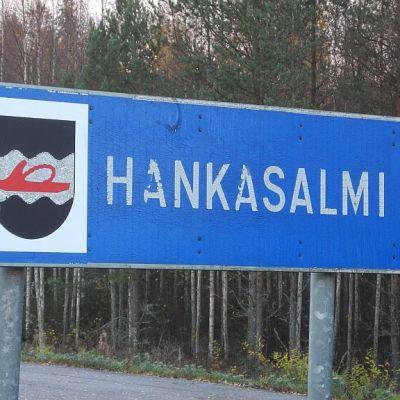 Hankasalmen kunnanrajakyltistä löytyy kunnanvaakuna, jossa onhopeahirsi ja vitsahankain.
