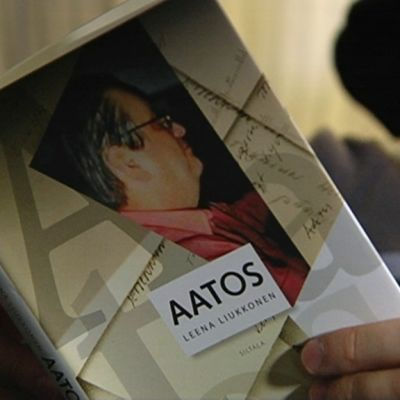 Mies lukee kirjaa Aatos Erkosta.
