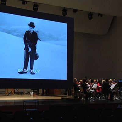 orkesteri, taustalla pyörii Chaplinin mykkäfilmi
