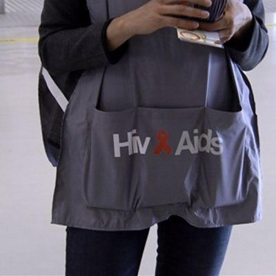 Kampanjahenkilö jakaa kondomeita kauppakeskuksessa.