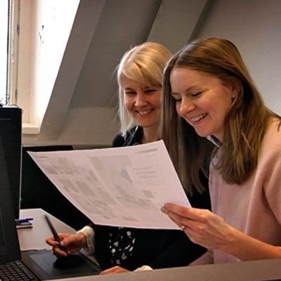 Costumen päätoimittaja Sanna Sierilä katselee A3-kokoista paperileiskaa yhdessä lehden AD:n kanssa.