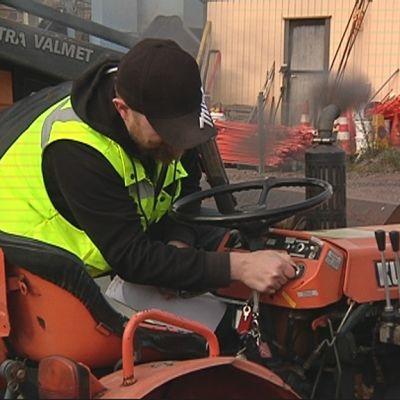 Mies käynnistää pientä traktoria.