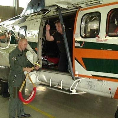 Mies tarkistaa pelastushelikopterin valjaita.
