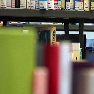 Nainen pälyilee kirjahyllyjen välissä.