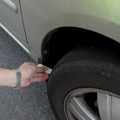 Poliisi mittaa auton renkaan kulutuspintaa.