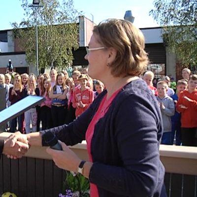 Mies kättelee naista kunniaplakaati toisessa kädessään. Taustalla Korian koulun oppilaita.