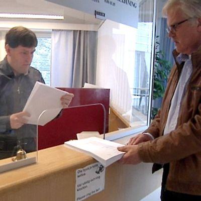 Kuvassa käräjäoikeuden infotiskillä ihmisiä saamassa papereita