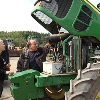 Kaksi ihmistä tutkiin traktorin moottoritilaa.