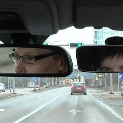 Kaksi naista autossa katsoo peruutuspeileihin.