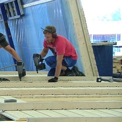 Kaksi työntekijää naulaa seinäelementtiä Kannustalon tehtaalla.