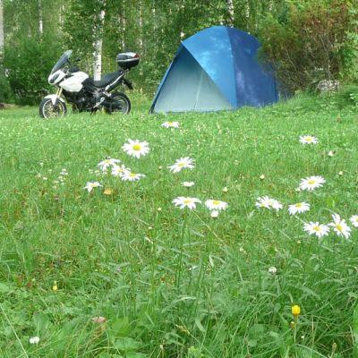 Teltta ja moottoripyörä leirintäalueella.