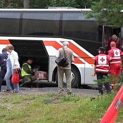 Ihmisiä linja-auton ulkopuolella. Myös Punaisen Ristin ihmisiä.