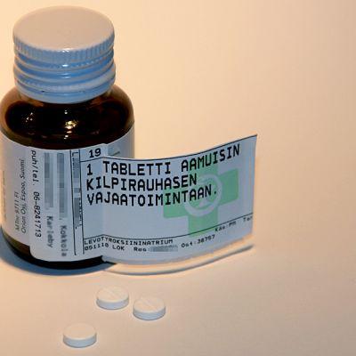 Kuvassa kilpirausalääkepurkki ja pillereitä sen edessä.