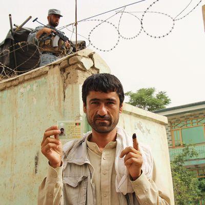 Mies esittelee korttiaan ja sormeaan, taustalla sotilas.