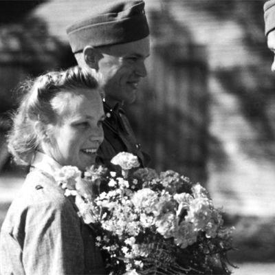 Tuore aviopari sotilas- ja lottapuvussa ottavat vastaan onnitteluja.