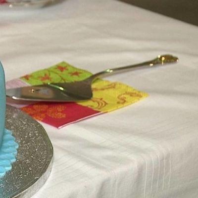 Turkoosiksi koristeltu kakku, jossa ruusuke päällä.