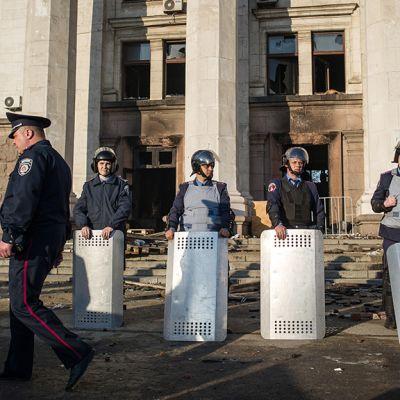 Ukrainalaiset poliisit vartioivat Odessassa palaneen ammattiliittorakennuksen edustalla.