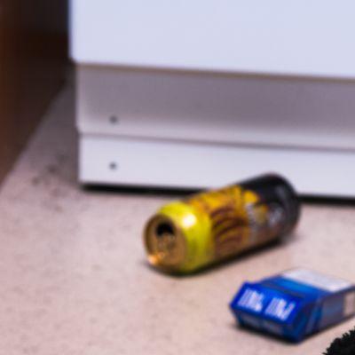 Lasten nalle, alkoholi juomatölkki ja tupakka aski lattialla