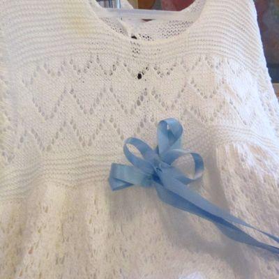 Kuvassa neulottu kastemekko sinisellä rusetilla