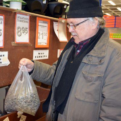 Kuvassa mies ja linnunruokapussi kaupassa