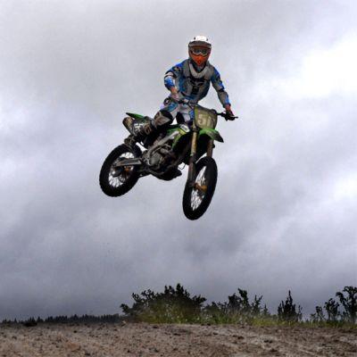 Motocross-kuski pyörineen korkealla ilmassa.