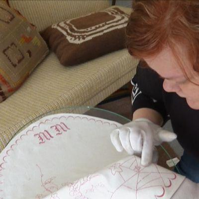 Museosuunnittelija Laura Lankinen tutkii tarjotinliinaa.