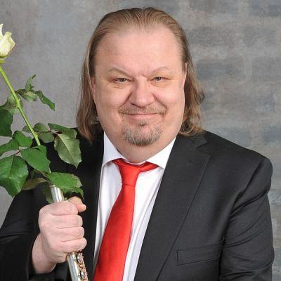 Jope Ruonansuu kädessää valkoinen ruusu ja huilu.
