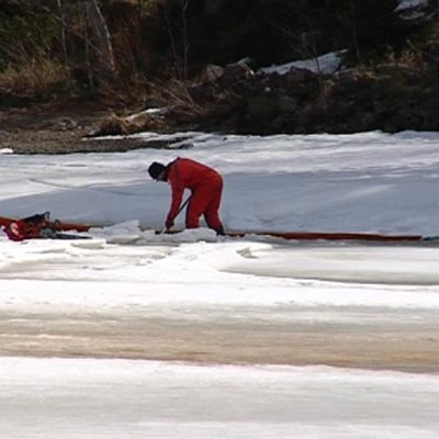 Öljyntorjuntapuomia ujutetaan jäähän tehtyyn railoon.