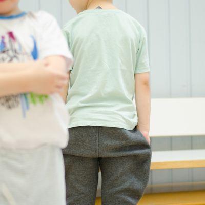 Lapsi kädet puuskassa etulallla. Toinen lapsi taustalla selkä kameraan päin kädet taskussa.