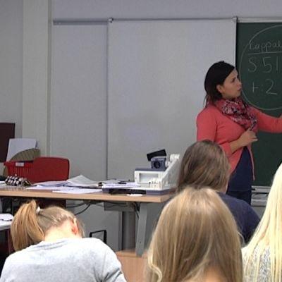 Opettaja seisoo luokan edessä ja opettaa biologiaa Cygnaeus-lukiossa.