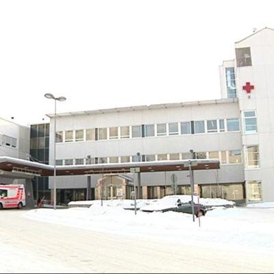 Pohjois-Karjalan keskussairaalan terveyskeskuspäivystysrakennus, jonka pihalla ambulanssi.